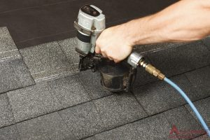 roofer lays asphalt shingles to install
