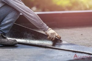 roofer lays down felt on flat roof
