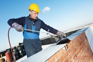 roofer installs felt to flat roof