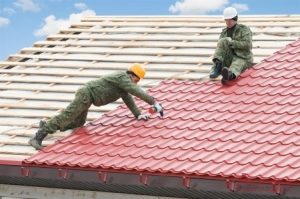 workers install red metal roof