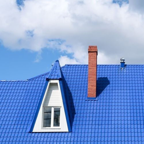 Roof with metal blue tiles, white triangle roof window and brown brick chimney against a blue sky with white clouds.