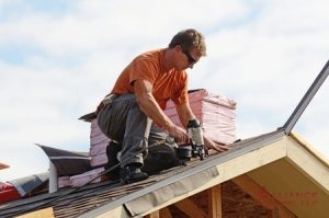 roofer nails shingles to roof