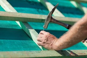 roofer hammers nail into roof