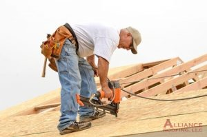 roofer nails wood to roof