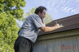 inspector makes notes during roof inspection