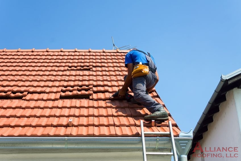 worker installs tile roof