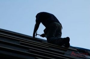 man hammers roof